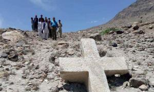A group of locals posing with the ancient cross in Pakistan.    Source: Pamir Times