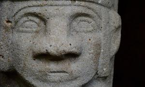 An ancient carved stone face of a megalithic statue in the San Agustín Archaeological Park, Colombia.