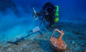 Diver Alexandros Sotiriou finds a ceramic table jug and a bronze rigging ring from the Shipwreck.