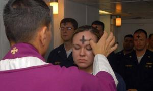 US Navy employees receive the sacramental ashes during an Ash Wednesday celebration.