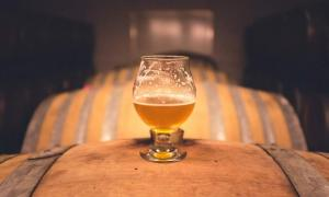 A glass of beer atop old barrels