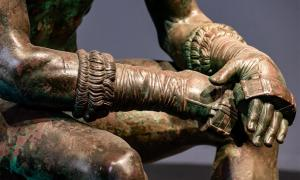Detail of The Boxer at Rest, Greek Hellenistic bronze sculpture of a sitting nude boxer at rest. Credit: giorgio / Adobe Stock
