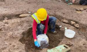 The Bronze Age burial urn about to be removed from where it was found, a tricky process!     Source: Fadó Archaeology