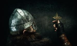 Viking holding Christian cross. Credit: Warpedgalerie / Adobe Stock