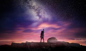 Man standing in a high place reaching up in wonder to the galaxy.