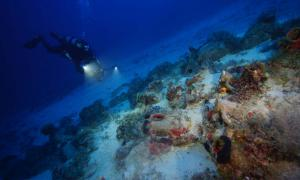 An archaeologist systematic photographs a wreck site to create a 3D site plan by Vasilis Mentogiani.