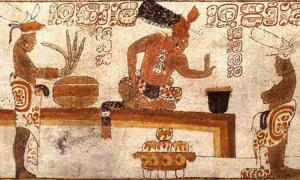 A Mayan lord sits before an individual with a container of frothed chocolate.