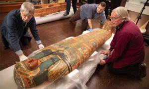 Dennis Piechota (from left), Adam Middleton, and Joe Green work on the ancient Egyptian coffin of Ankh-Khonsu with a team at the Semitic Museum. Source: Kris Snibbe / Harvard Gazette.