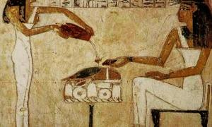 Painting of an ancient Egyptian woman being served beer.