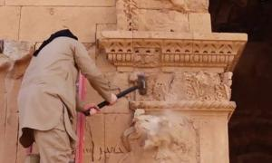 An Islamic State militant destroying artifacts in Iraq's World Heritage city of Hatra