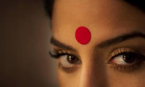 Close-up of a woman's eyes and red bindi.