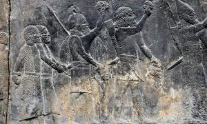 "Assyrian soldiers carry beheaded heads of their prisoners as depicted on a wall in the South-West Palace at Nineveh, during the ""First"" Fall of Neneveh.          Source: Osama Shukir Muhammed Amin / CC BY-SA 4.0"
