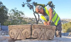 Director of the Jerusalem Promenade excavation Yaakov Billig with the unearthed capitals that likely were part of a First Temple Period palace.            Source: Yoli Shwartz / Israel Antiquities Authority
