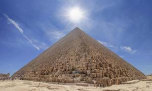 The Pyramid of Cheops illuminated by the sun in backlight, with people entering inside to visit it. The area with the great pyramids of Giza, Egypt. Source: Alfredo /Adobe Stock