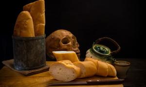 Grinding bones into bread - human skull and fresh bread.