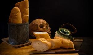 Grinding bones into bread - human skull and fresh bread.