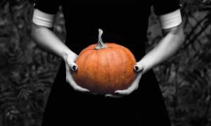 A ghostly pale woman holding a pumpkin. Halloween and paranormal phenomena often go hand in hand.