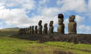 Restored statue platform with standing moai on the south coast of Rapa Nui. Note that one of the moai is adorned with a red scoria pukao.