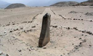 The monolith called Huanca with pyramids in the background in Caral-Supe
