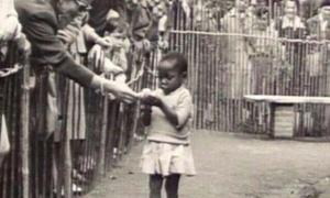 An African girl is shown at the 1958 Expo in Brussels, Belgium that featured a 'Congo Village' with visitors watching her from behind wooden fences