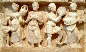 Hellenistic culture in the Indian subcontinent: Greek clothes, amphoras, win,e and music. Detail from Chakhil-i-Ghoundi Stupa, Hadda, Gandhara, 1st century AD.