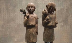 Wooden funerary figurines of Khitan people returning from a hunt. Liao dynasty (907–1125). Held at the Capital Museum, Beijing. (BabelStone/CC BY SA 3.0) Background: Stone tablet with fake epitaph inscription in the Khitan Large Script. Held at the Nationalities Museum of the Inner Mongolia University, but not on official display. It is an almost complete copy of the Epitaph for the Princess of Yongning Commandery (永寧郡公主墓誌銘) of 1092.