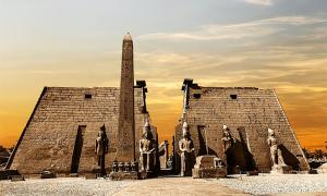 Entrance to the Luxor Temple at sunset showing the obelisk and statues of pharaohs