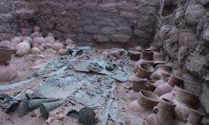 A rich Moche grave with elaborate copper artifacts and several ceramic vessels.