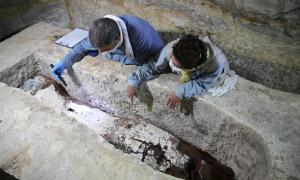 Archaeologists examine a mummy at the Mummification Workshop in Saqqara. Credit: Ministry of Tourism and Antiquities.
