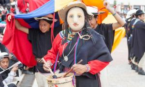 A masked woman leads a procession as part of the ceremony of Pawkar Raymi.