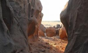 Man-made holes visible amongst the natural erosion features of the granite rock in Sudan
