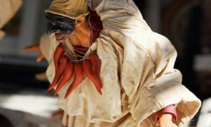 A figurine of Pulcinella with his mask