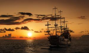 Pirate ship on the open sea at sunset. Representative image of the Queen Anne's Revenge.