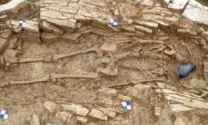 One of the Roman slave skeletons alongside a pot found at the burial site in Somerset, England. Source: Wessex Archaeology