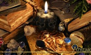 Ancient Sorcery: Antique witch book, black candle and ritual objects.