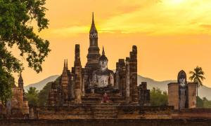 Ancient pagoda and big buddha at Sukhothai Historical Park, the birthplace of the Sukhothai Kingdom. Source: somrakjendee / Adobe Stock.