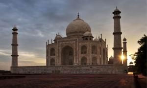 The sun rises behind the Taj Mahal