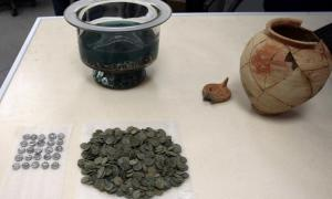 The ancient Roman coins, dating to the 1st century AD alongside the clay vessel in which they were found; the owner's name is inscribed on the vessel.