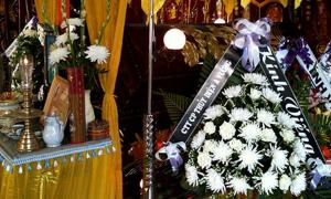 Decorations placed around a coffin at a home funeral in Da Nang, Vietnam. At left, placed in front of the coffin, is an altar featuring a framed photo of the deceased and a pot for offering joss sticks. At right are a number of flower bouquets with attached condolences, and in the background are a number of vertical banners, also offering condolences.