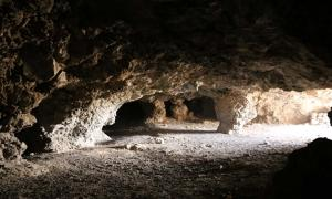 """View of the """"Cueva del Pirul"""", one of the largest systems of interconnected caves to the East of the Pyramid of the Sun. One can notice the many rough pillars left to support the roof and a number of side passages branching out in different directions."""