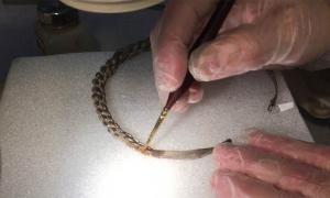 A piece of the Viking silver treasure hoardbeing cleaned by a conservator.      Source: Acta Konserveringscentrum AB