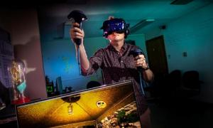 Computer science graduate student and project manager Cameron Merrill explores a virtual archaeology cave excavation experience he helped create. Source: Fred Zwicky / University of Illinois