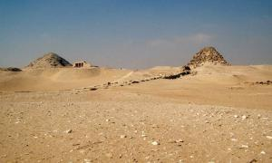 A general view of the ancient Egyptian necropolis at Abu Sir. The pyramid of Sahure is in the forground with the causeway leading up to it. Visible further back is the mastaba of Ptah Shepsus and all the way towards the back is the pyramid of Neferirkare.