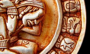 Closeup of glyphs on a Mayan calendar. Credit: zimmytws / Adobe Stock