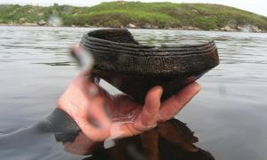 A diver holds a Neolithic ca. 3,500 BC Ustan vessel found near a crannog in Loch Arnish, Scotland.      Source: C Murray/ Antiquity