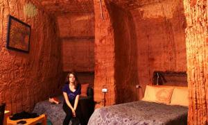 A woman sits in an underground hotel room in Coober Pedy