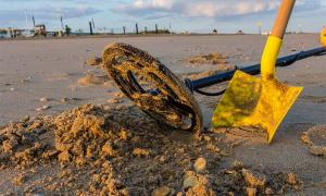 A metal detector and shovel on the beach with coins that might be rare medieval coins. You never know!        Source: andrewbalcombe / Adobe Stock