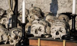 Skulls painted with names, colorful flowers, and crosses in the Charnel House in Hallstatt, Austria. Source: J. Ossorio Castillo / Adobe.