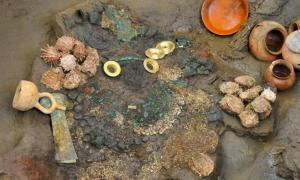 Gold earrings, two knives, a collection of shells, and ceramic containers were uncovered from a flooded Lambayeque tomb.