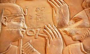 Relief carved from stone featuring Ptolemy XIII of Egypt and the deity Isis. Representational image.